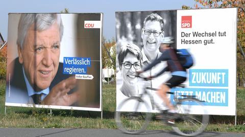 Wahlplakate zur Landtagswahl in Hessen in Darmstadt, Volker Bouffier und Thorsten Schäfer-Gümbel sind zu sehen, während im Vordergrund ein Fahrradfahrer vorbeifährt